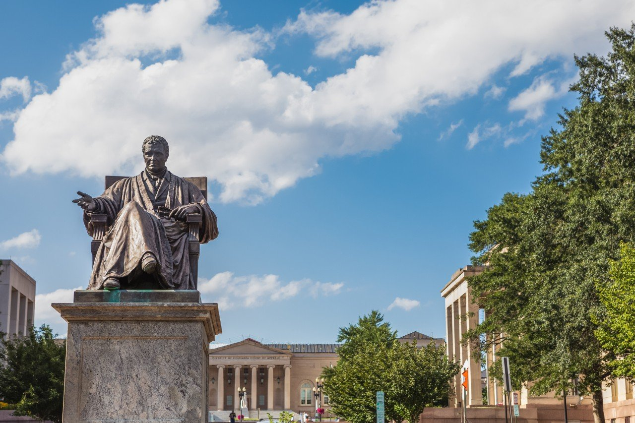 Bronze sculpture of John Marshall, fourth Chief Justice of the U.S. Supreme Court, located in John Marshall Park in Washington, DC with DC Court of Appeals in the background. It was sculpted by artist William Wetmore Story in 1883.