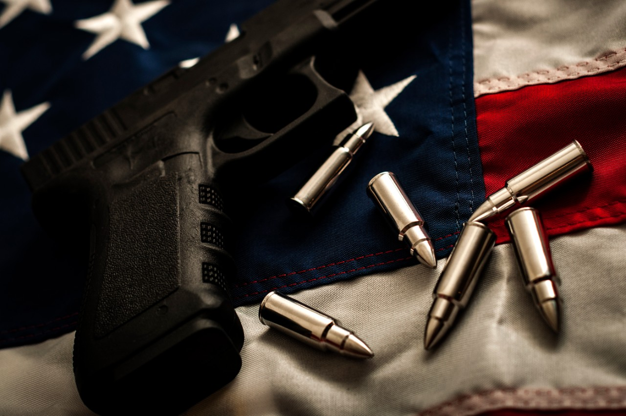 The second amendment and the right to bare arms concept with a grungy image of a gun and bullets on american flag. In the United States of America the 2nd amendment protects people's right to own guns