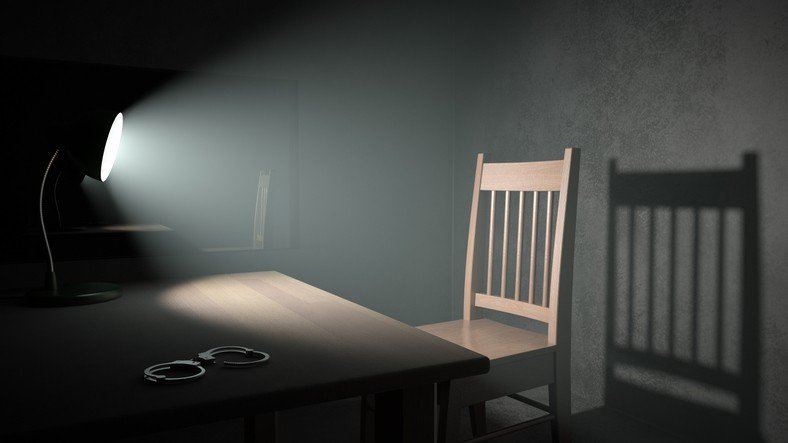A spotlight pointing at an empty chair in a dark interrogation room. Very detailed high resolution 3D render.