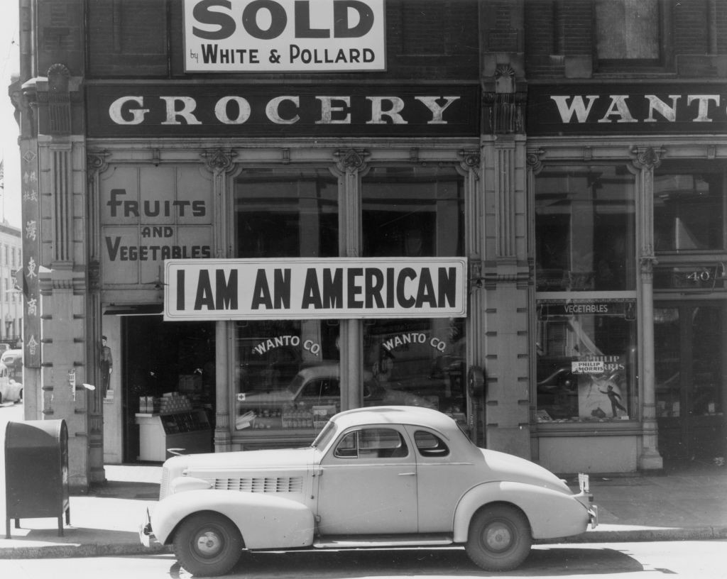 A sign reading: 'I AM AN AMERICAN', on the Wanto Co grocery store at 401 - 403 Eighth and Franklin Streets in Oakland, California, the day after the attack on Pearl Harbor, 8th December 1941. The store was closed and the Matsuda family, who owned it, were relocated and incarcerated under the US government's policy of internment of Japanese Americans. The sign was installed by Tatsuro Matsuda, a University of California graduate. (Photo by Dorothea Lange/Getty Images)