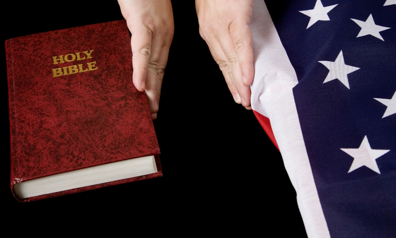 Separation of Church and State concept: Hands pushing a Bible away from an American flag